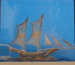 Small silver filigree sailing vessel in glass display case, of oriental design.
