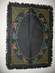 Rectangular black, fringed cloth with delicate painting of flowers surrounded by trellising.
