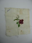 Square, cream cloth with embroidered red rose and 'Dorris' written in one corner.