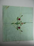 Rectangular piece of green silk decorated with embroidered red roses and yellow ribbon. The words 'To Dorris' are written in one corner.