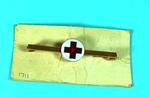 Gold brooch pin with red cross on white background