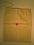 Small drawstring bag made of calico, with a label sewn on the front: 'Gift of the British Junior Red Cross'