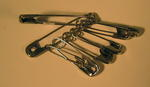 Eight safety pins of various sizes.