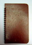 Small spiral-bound notebook, lined pages, brown cover.