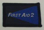 Navy and blue cloth flash, to be worn on uniform by Red Cross Junior who holds a certificate in First Aid. With the words 'First Aid 2' in white.