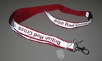 Reflective ribbon/lanyard to go around neck, with the words 'British Red Cross' and 'www.redcross.org.uk/firstaid' in red. With plastic fastener and metal hook.
