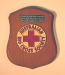 Small wooden shield gifted to the British Red Cross by the Australian Red Cross Society to commemorate the 75th Anniversary Tour in September 1989