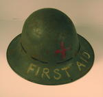 metal helmet with emblem painted on front and 'FIRST AID' in white lettering