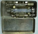 Syringe in a tin