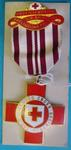 Red/white and gold coloured badge with red cross pendant hanging from ribbon. Ribbon is white with 5 vertical dark red lines. Top piece features a red cross and gold text on red background.