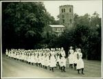 Photograph of a group of female VADs in indoor uniform marching through a field, past a church.