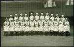 photograph of a group of female VADs in indoor uniform, seated inside a hall
