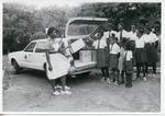 VAD cadets and Junior Red Cross members from the Antigua Branch of the British Red Cross distributing food supplies to children in the community of the City of St John's