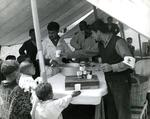 Black and white photograph. Milk distribution station for Algerian refugees at Beni Drar, children and Red Cross team under a tent.