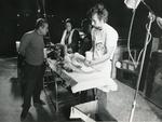 Black and white photograph from Red Cross News June 1976 of a doctor from the ICRC treating a young victim from the conflict in Lebanon
