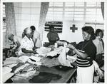 Black and white photograph of the Jamaican Red Cross sorting out clothing for victims of a Honduras hurricane